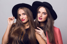 Close Up Beauty  Fashion Image Of Two Girls, Sisters, Posing On Grey Background, Hugging, Smiling. Wearing Stylish Pink  Coat And Black Hat, Short Top And Evening Dress.