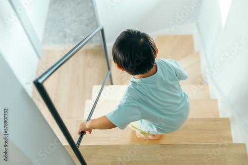 Fototapeta 小さい男の子が家の階段を勢いよく降りている後ろ姿 kids boy