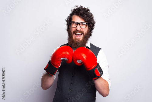 Portrait of young bearded man wearing suit screaming and boxing with boxing gloves