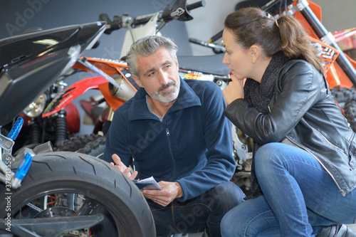 male motorbike seller talking with female customer near motorbike