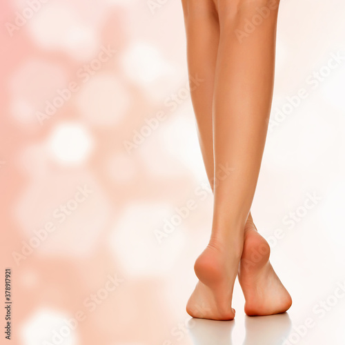 Beautiful female legs against an abstract background with sun flares and copyspace. #378917921