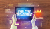 Fototapeta Kawa jest smaczna - Close-up of hands holding tablet with EMPLOYEE ENGAGEMENT inscription, modern business concept