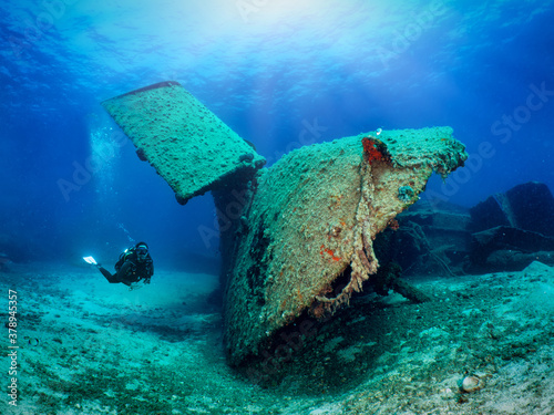 Fotomural A scuba diver explores a sunken shipwreck in shallow waters of the Aegean Sea, G