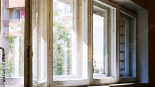 Fotografie, Obraz old white window with wooden cracked frame and sunlight through glass to home