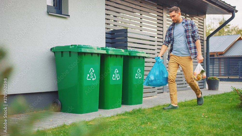 Fototapeta Caucasian Man is Walking Outside His House in Order to Take Out Two Plastic Bags of Trash. One Garbage Bag is Sorted as Biological Food Waste, Other is Recyclable Bottles Garbage Bin.