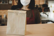 Leinwandbild Motiv waitress wearing protection face with dessert paper set bag on counter bar waiting for customer in modern cafe coffee shop, food delivery, cafe restaurant, takeaway food, small business owner concept