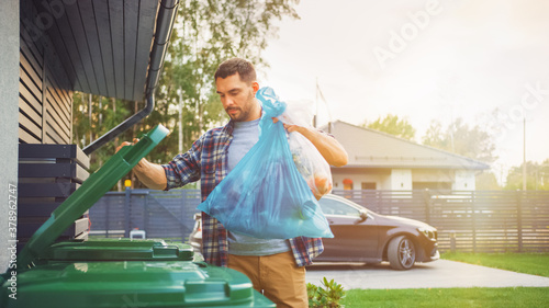 Photo Caucasian Man is Throwing Away Two Plastic Bags of Trash next to His House