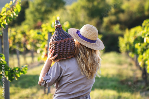 Tela Woman with demijohn at vineyard