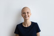 Profile picture of smiling young hairless sick woman struggle fight with oncology isolated on grey studio background. Headshot portrait of bald ill female patient suffer from cancer, beat sickness.