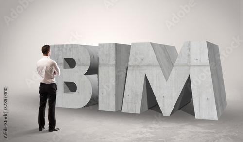 Rear view of a businessman standing in front of BIM abbreviation, modern technol Wallpaper Mural