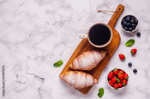 Fototapeta Breakfast with croissants and fresh fruits.