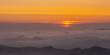 """Na zdjęciu """"ocean"""" chmur unoszących się swobodnie między szczytami gór."""