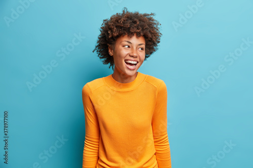 Obraz na plátně Positive cheerful young African American woman laughs positively and looks aside concentrated happily dressed in casual orange jumper isolated on blue studio background