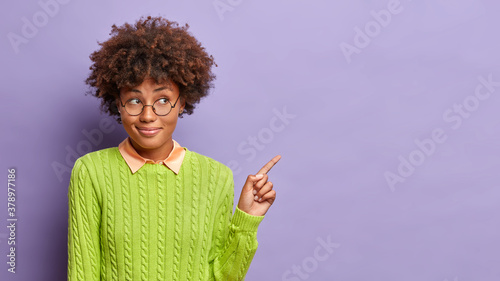 Fototapeta Attractive curious African American woman points on blank space shows place for your advertisement or promotional content wears round glasses and green sweater poses against purple background obraz