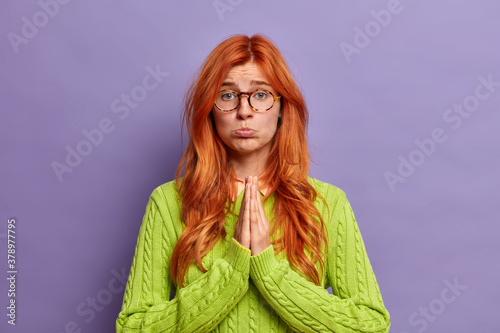 Fotografie, Obraz Beautiful sad woman with pleading expression, keeps palms pressed together in pray and looks innocent at camera