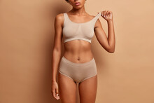 Femine Beauty Lines Concept. Slim Woman With Dark Skin Flat Stomach Wears High Waist Panties And Bra. Female Model Poses In Underwear Against Brown Background