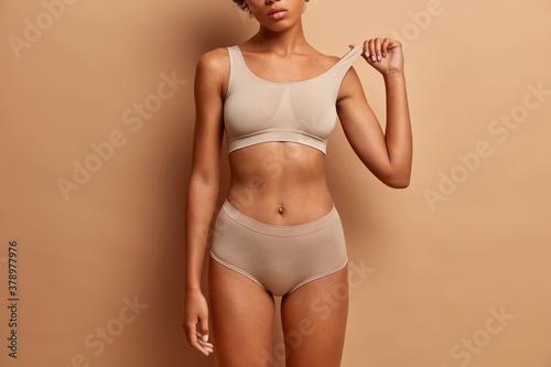 Fototapeta premium Femine beauty lines concept. Slim woman with dark skin flat stomach wears high waist panties and bra. Female model poses in underwear against brown background
