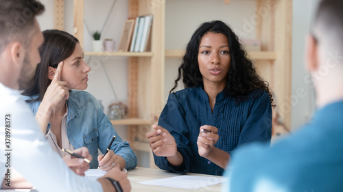 African American businesswoman mentor coach speaking, training staff at meeting, sitting at table in boardroom, female employee sharing ideas, discussing project strategy with colleagues - 378978373