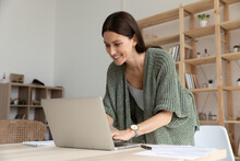 Interested Smiling Young Businesswoman Standing Near Table In Modern Office, Using Laptop, Positive Female Employee Looking At Screen, Writing Email, Chatting, Working On Online Project