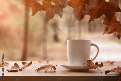 Photo Mug with hot drink on wooden table with autumn landscape