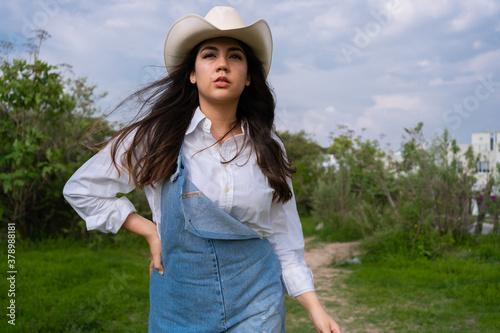 Fototapeta La joven está con su sombrero en una zona verde mirando al frente