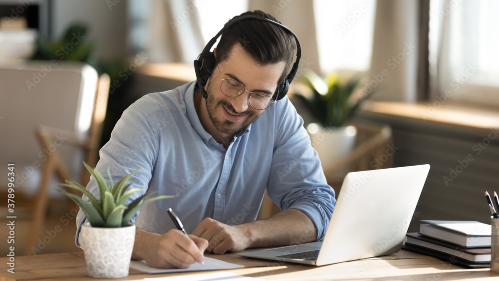 Fototapeta Smiling young Caucasian man in headphones glasses sit at desk work on laptop making notes. Happy millennial male in earphones watch webinar or training course or computer, study online from home.