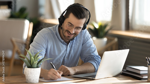 Obraz Smiling young Caucasian man in headphones glasses sit at desk work on laptop making notes. Happy millennial male in earphones watch webinar or training course or computer, study online from home. - fototapety do salonu