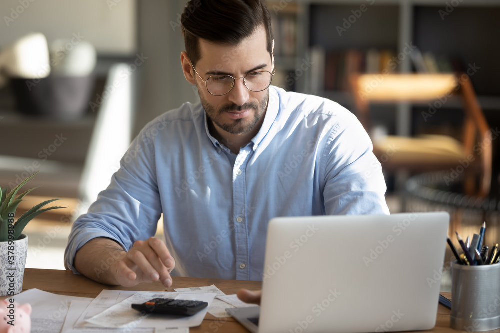 Fototapeta Focused young Caucasian man look at laptop screen calculate expenses expenditures pay bills taxes online. Millennial male busy managing household family budget, take care of financial paperwork.