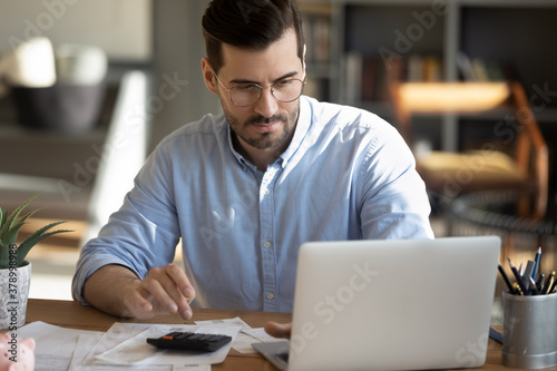 Focused young Caucasian man look at laptop screen calculate expenses expenditures pay bills taxes online. Millennial male busy managing household family budget, take care of financial paperwork.