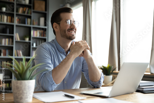 Fototapeta Overjoyed young Caucasian male worker sit at desk at home office distracted from computer work laughing joking. Happy millennia man using laptop have fun dreaming or thinking of job career success. obraz