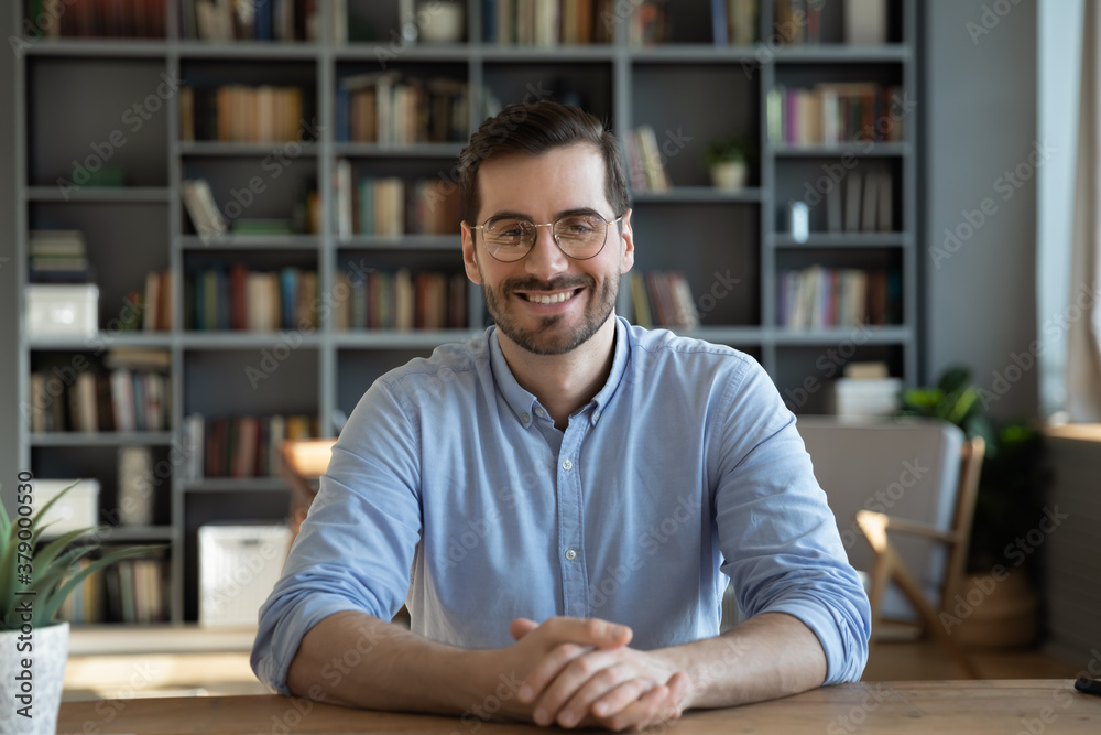 Fototapeta Headshot portrait of smiling 30s Caucasian millennial man in glasses sit at desk at home talk speak on video call or webcam virtual conference. Picture of happy young male in spectacles pose at table.