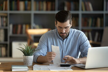 Focused Young Caucasian Man Sit At Desk At Home Manage Household Expenditures Expenses Paying Bills Online. Millennial Male Analyze Consider Home Budget, Calculate On Machine. Economy Concept.