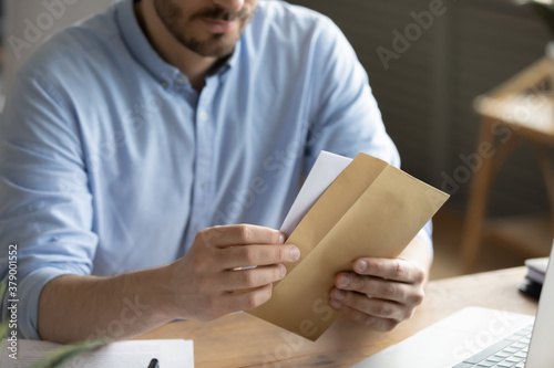 Fototapeta Crop close up of man sit at desk open envelope with paper letter or correspondence at office. Male worker get postal paperwork or notice notification at workplace, receive message or invitation. obraz
