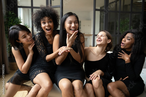 Smiling young chinese 20s pretty girl showing engagement diamond ring to excited diverse female best friends, celebrating hen bachelorette shower party together in black cocktail classy dresses.