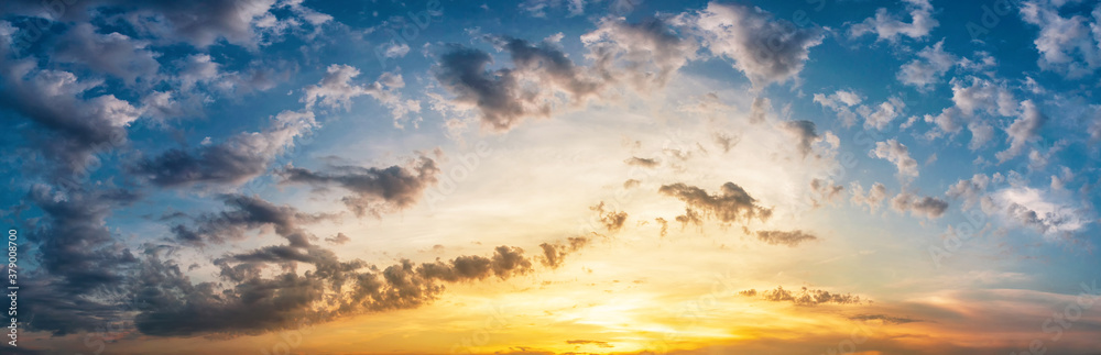 Fototapeta Panorama of dramatic sky with clouds at yellow-orange sunset.