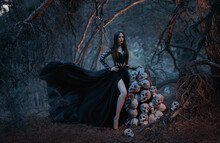 A Gothic Beautiful Young Woman In A Black Dress Stands Near A Mountain Of Human Skulls. Fashion Model In The Image Of The Goddess Of Death In A Dark Forest Of Trees. Silk Fabric Flies In The Wind