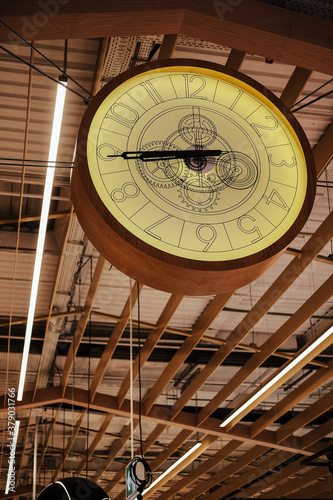 Photo Vertical low angle shot of a big clock hung from a ceiling