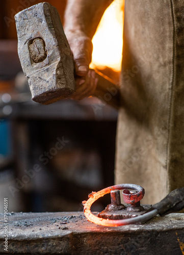 Fototapeta Close up blacksmith is processing a hot metal object of a spiral shape at anvil in a workshop obraz