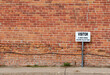 Antique grungy reddish brown brick wall texture background in a common bond brickwork pattern, with a visitor parking sign and copy space