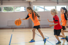 Kids In Bright Sportswear Playing Basketball Together And Feeling Energized