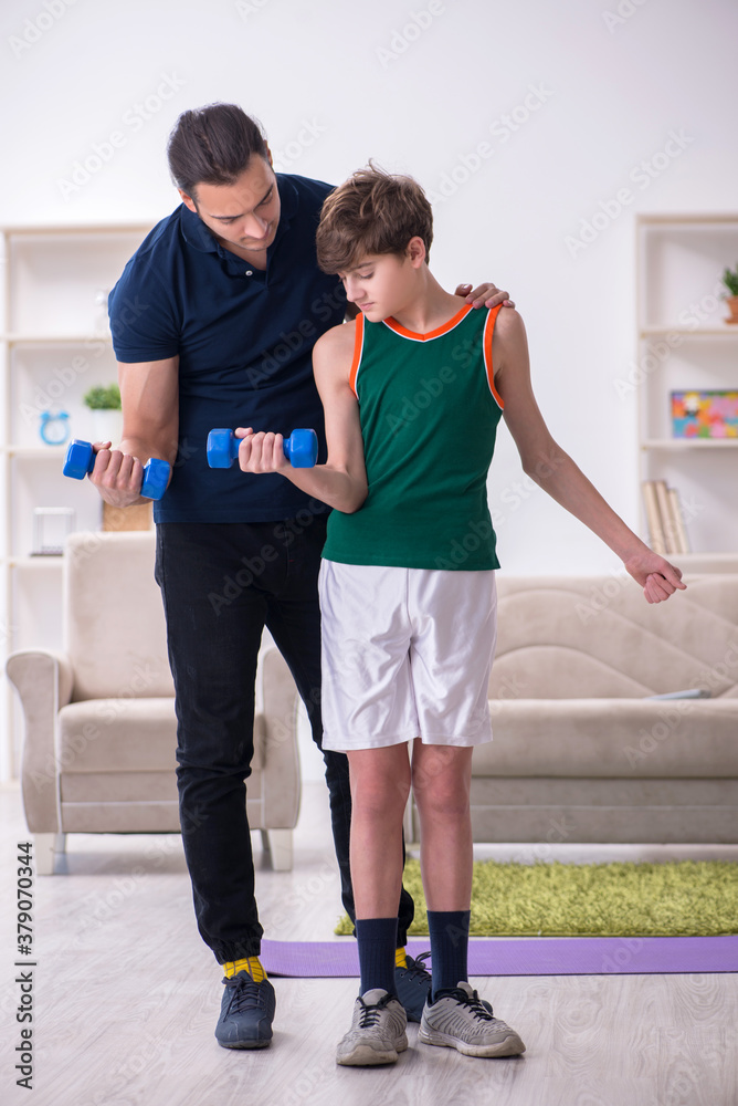 Fototapeta Father and son doing sport exercises indoors