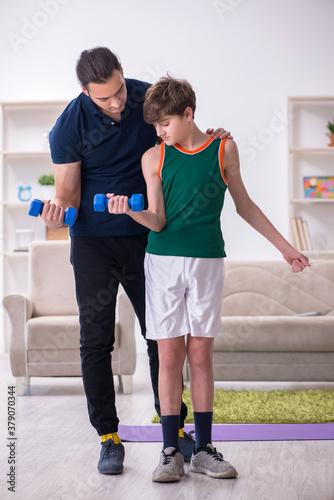 Fototapeta Father and son doing sport exercises indoors obraz