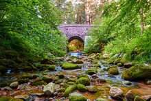 Bridge Of Gray Stones Lined With Green Trees, Beautiful Stones In A Reddish River. Germany.
