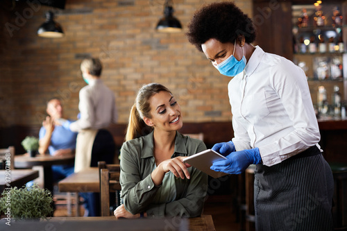 Fotografiet Black waitress with face mask taking order on touchpad from a customer in a cafe