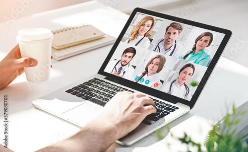 Fototapeta Man drinking coffee during video chat with doctors obraz na płótnie