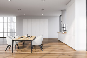 White kitchen with dining table, side view