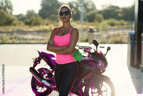 Seductive young woman in pink t-shirt poses near sport motorcycle at self service car wash in the morning.