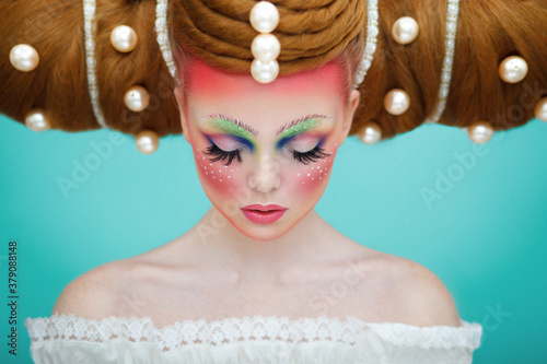 Fototapeta Closeup portrait of a female model with a creative colorful makeup and hairstyle with huge pearls. The concept of hairdressing art. obraz