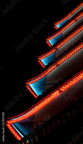 Fotografiet Neon patterned lighting of a pagoda with red and blue lighting on a black background