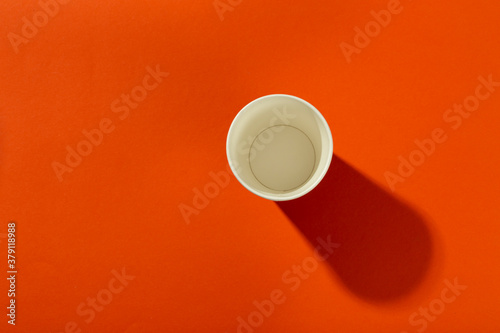 Fototapeta Paper cup for coffee on an orange background. Coffee to go. obraz